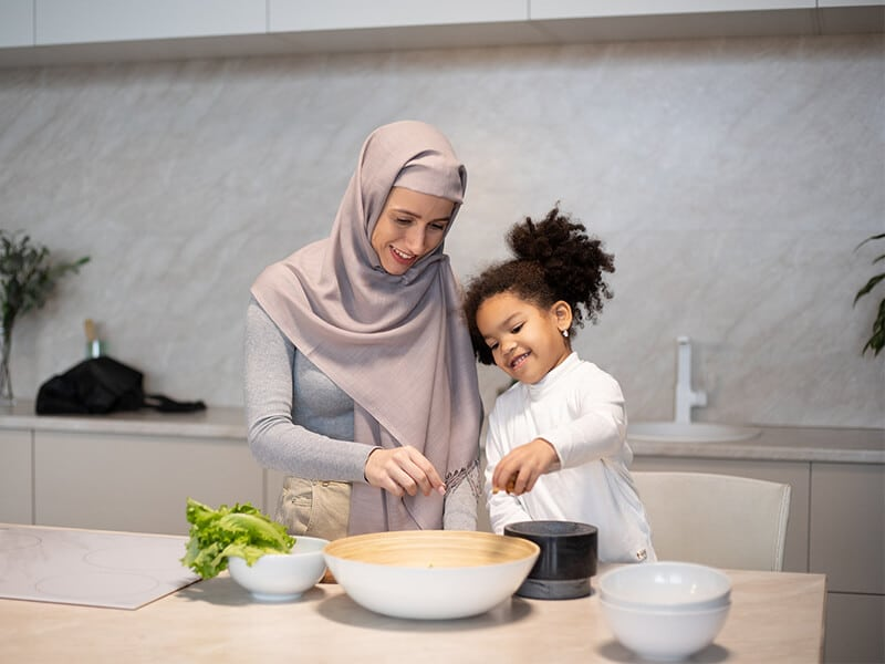 mom mixing food in bowl with daughter