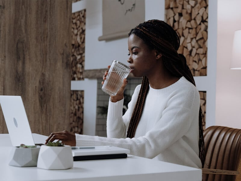 woman drinking water in front of laptop 1
