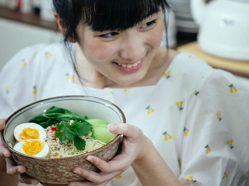 woman eating rice porridge